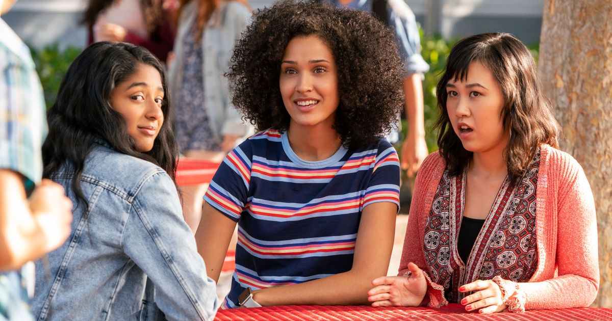 Devi, an Indian teenager who is the main character of Never Have I Ever, sits across from her two friends, Fabiola, a black teenager, and Eleanor, an Asian teenager.
