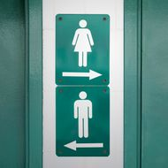 Green sign with male and female symbols directed to go in opposite directions