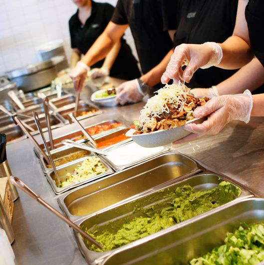 Employees prepare orders for customers at a Chipotle Mexican Grill Inc. restaurant in Hollywood, California, U.S., on Tuesday, July 16, 2013.