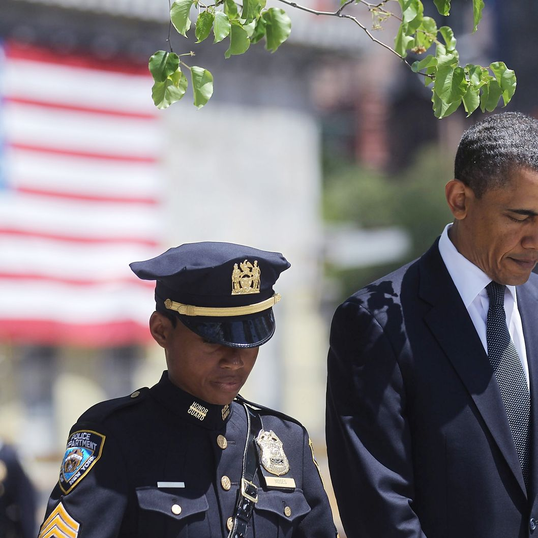 President Barack Obama (R) and New York Police Department officer Stephanie Moses bow their heads at a wreath laying ceremony at Ground Zero, after Osama bin Laden was killed on May 5, 2011 in New York City. Obama also visited a New York Fire Department firehouse and met with families of victims of the terrorist attack on September 11, 2001during his visit to New York.