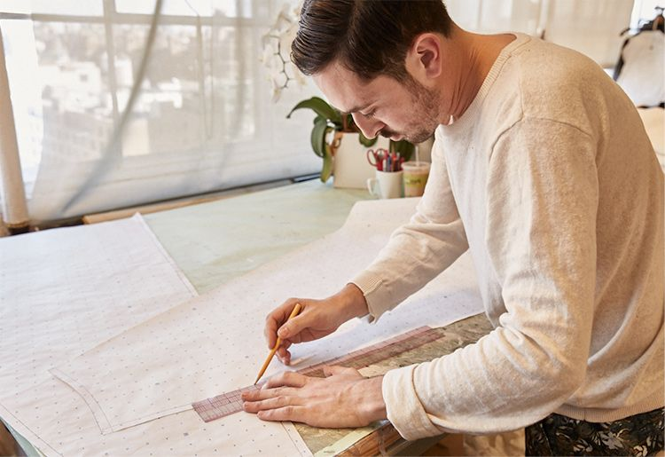 Man tracing outline on paper dress mock