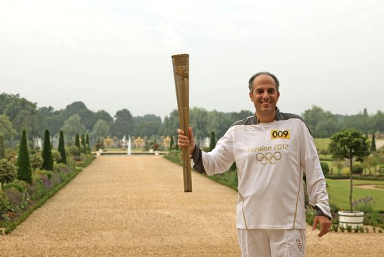 LONDON, UNITED KINGDOM - JULY 27:  In this handout image provided by LOCOG, Torchbearer 009 Mark Levy holds the Flame in the grounds of Hampton Court Palace during the final day on July 27, 2012 in London, England. The Olympic Flame is now on Day 70 of a 70-day relay involving 8,000 torchbearers covering 8,000 miles.  (Photo by LOCOG via Getty Images)