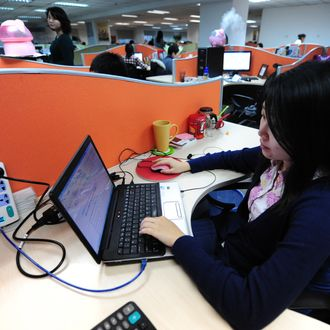 To go with AFP story by Francois Bougon: LIFESTYLE-CHINA-US-IT-INTERNET-GOOGLEA woman works online in her cubicle at an office in Beijing on February 4, 2010. China's homegrown social media sites like Weibo are booming thanks to their better knowledge of the world's largest Internet market, and the censorship stifling foreign rivals like Facebook, Twitter, and Google-owned YouTube. AFP PHOTO/Frederic J. BROWN (Photo credit should read FREDERIC J. BROWN/AFP/Getty Images)