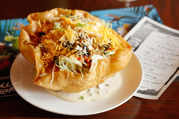 Tanner's taco salad is made with ground beef, black olives, lettuce, cheddar, sour cream, tomato, and beans.