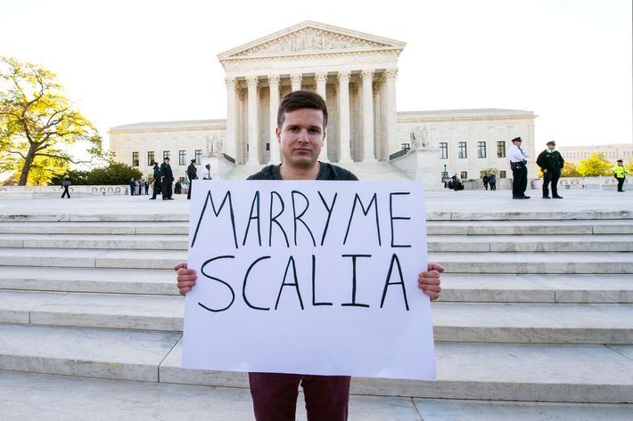 RYAN AQUILINA holds a sign as pro and anti-gay marriage demonstrators rally outside the U.S. Supreme Court on the morning that oral arguments on the question of same sex marriage are heard.