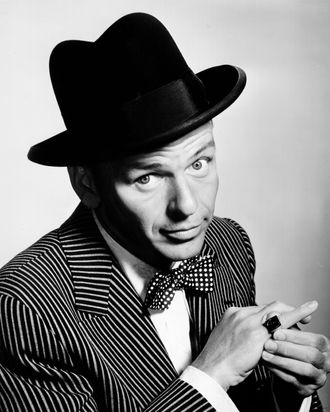 Pop singer Frank Sinatra poses for a portrait sporting a hat and bow tie and showing off a ring on his pinky in circa 1950.