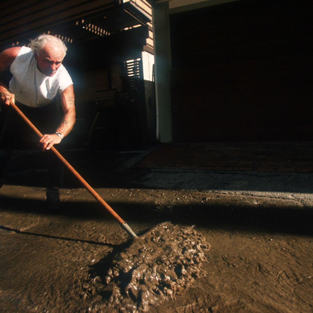 A man shovels away mudslide debris after an El Nino rainstorm February 9, 1998 in Malibu, CA. Million-dollar homes sustain damage or are completely destroyed after an El Nino rainstorm leads to erosion that causes a cliff to buckle.