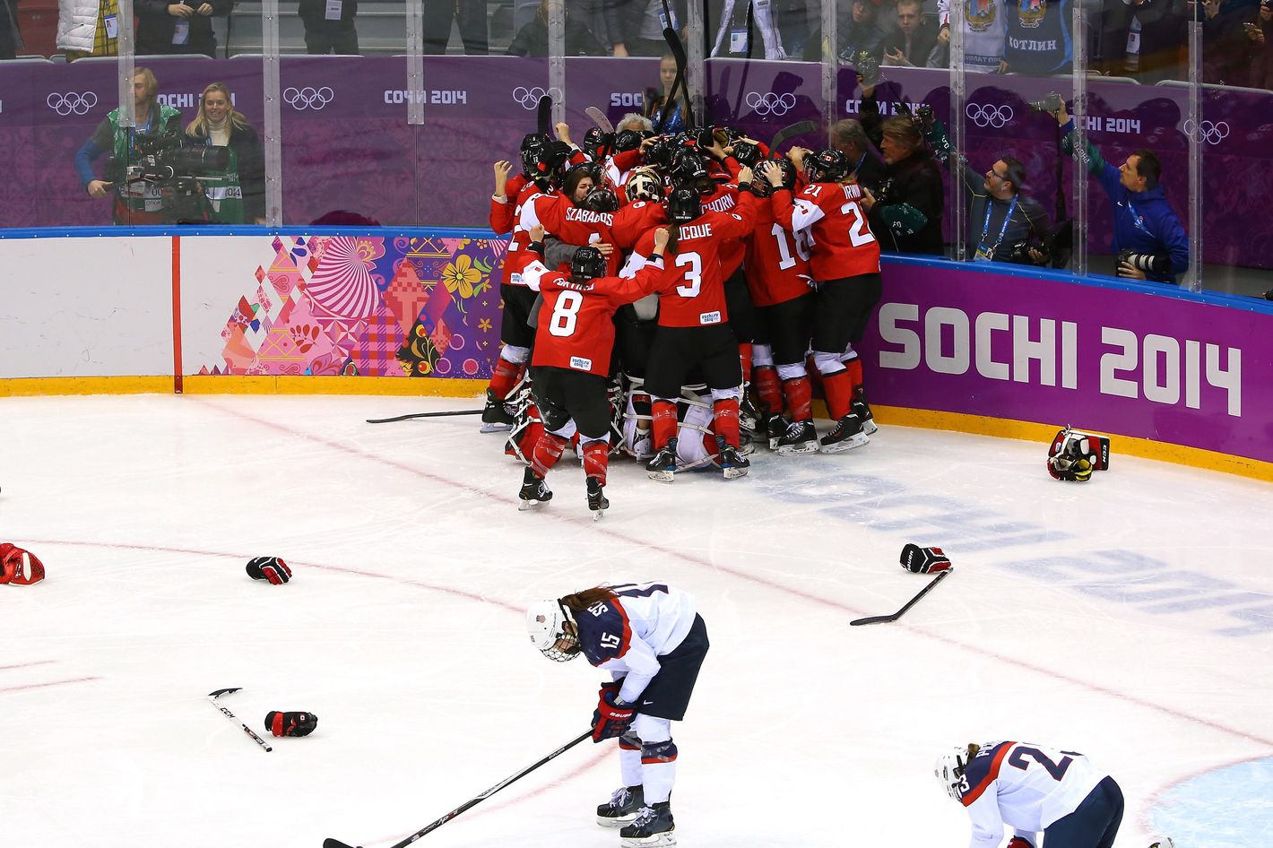 Marie-Philip Poulin #29 of Canada celebrates with teammates after scoring the game-winning goal against the United States in overtime as Anne Schleper #15 and Michelle Picard #23 of the United States react during the Ice Hockey Women's Gold Medal Game on day 13 of the Sochi 2014 Winter Olympics at Bolshoy Ice Dome on February 20, 2014 in Sochi, Russia.