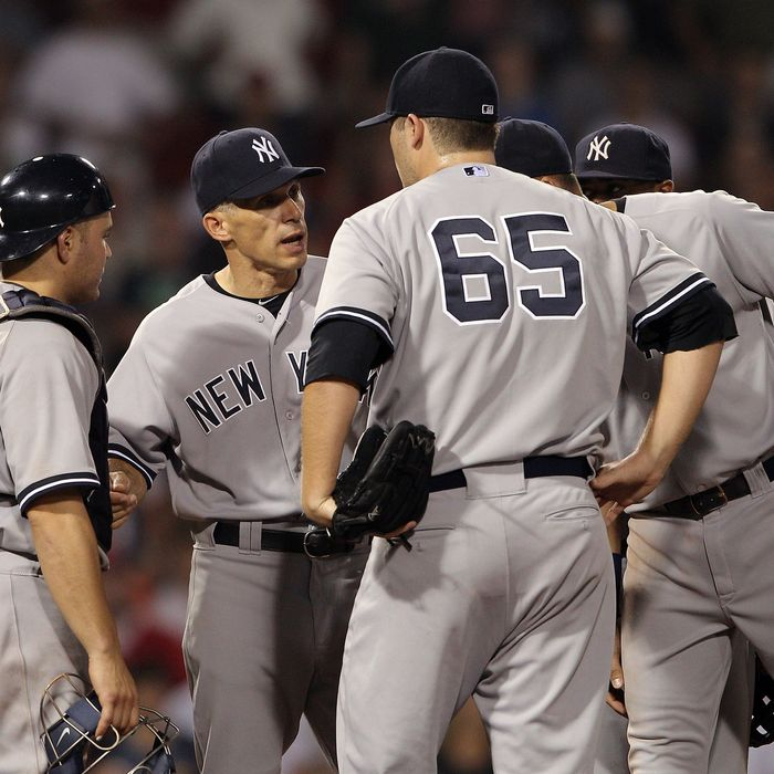 BOSTON, MA - AUGUST 08: Joe Girardi #28 talks with Russell Martin #55, Phil Hughes and Derek Jeter #2 in the 10th inning against the Boston Red Sox on August 8, 2011 at Fenway Park in Boston, Massachusetts.The Boston Red Sox defeated the New York Yankees 3-2 in 10 innings. (Photo by Elsa/Getty Images)