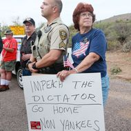 ORACLE, AZ - JULY 15: An anti-immigration activist stands next to a Pinar County Sheriff's deputy during a protest along Mt. Lemmon Road in anticipation of buses carrying  illegal immigrants on Jully 15, 2014 in Oracle, Arizona.  About 300 protesters lined the road waiting for a busload of illegal immigrants who are to be housed at a facility in Oracle. (Photo by Sandy Huffaker/Getty Images)