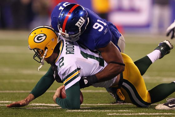 EAST RUTHERFORD, NJ - DECEMBER 04:  Aaron Rodgers #12 of the Green Bay Packers is sacked by Justin Tuck #91 of the New York Giants in the seocnd quarter at MetLife Stadium on December 4, 2011 in East Rutherford, New Jersey.  (Photo by Al Bello/Getty Images)