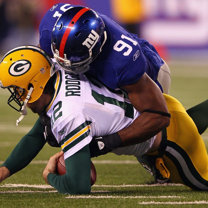 Aaron Rodgers #12 of the Green Bay Packers is sacked by Justin Tuck #91 of the New York Giants in the second quarter at MetLife Stadium on December 4, 2011 in East Rutherford, New Jersey.
