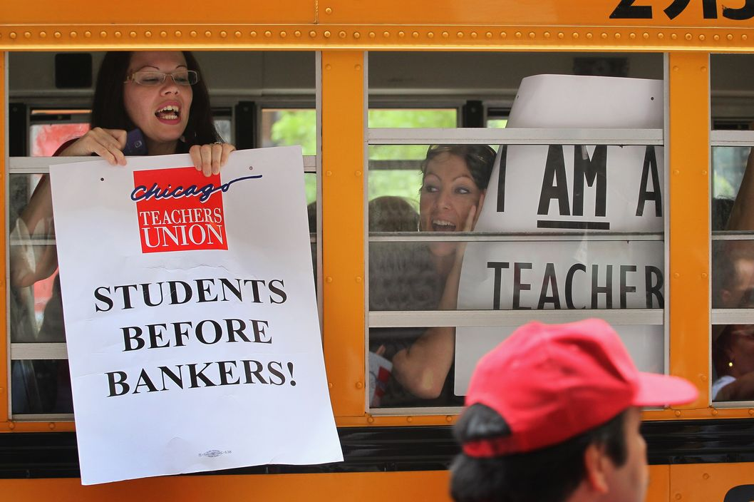 CHICAGO, IL - JUNE 22:  Chicago school teachers display protest signs from inside a school bus as they leave a demonstration outside the Chicago Board of Education building on June 22, 2011 in Chicago, Illinois. Hundreds of teachers demonstrated outside the board's offices and marched through the city's financial district to protest the board's recent decision to rescind a 4 percent annual raise promised to the teachers in their contracts.   (Photo by Scott Olson/Getty Images)