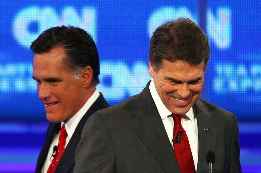 TAMPA, FL - SEPTEMBER 12:  Republican presidential candidate Mitt Romney walks behind Gov. Rick Perry during a break in a presidential debate sponsored by CNN and The Tea Party Express at the Florida State fairgrounds on September 12, 2011 in Tampa, Florida. The debate featured the eight candidates ten days before the Florida straw poll.  (Photo by Win McNamee/Getty Images)