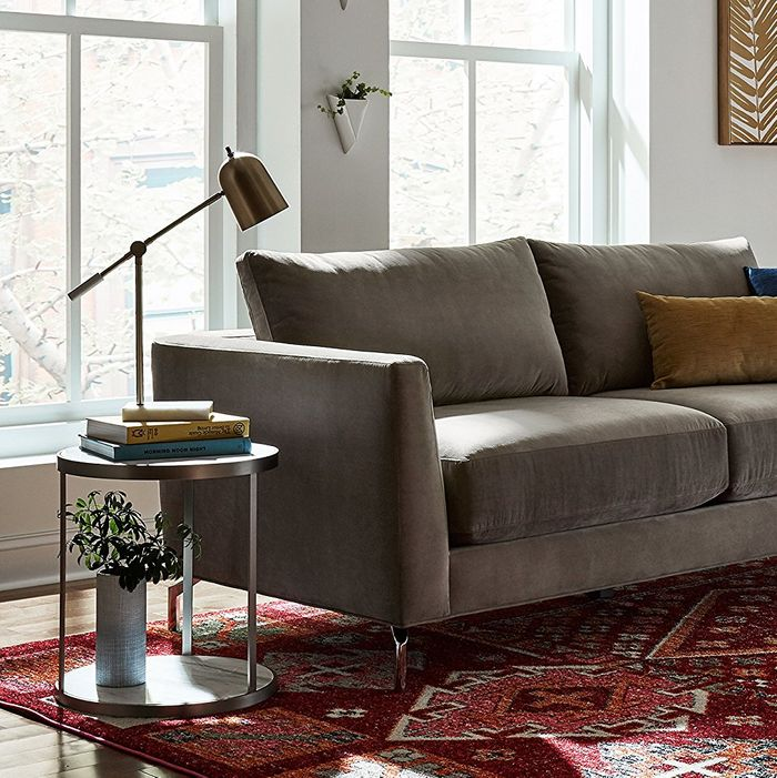 A Wayfair large desk lamp on a side table next to a grey couch on top of a dark red patterned rug. The Strategist - Very Tasteful Lamps from Amazon's Rivet and Stone and Beam Are on Sale