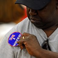 "Ricky Tyler puts his ""I Voted"" sticker on after casting his ballot at John Fremont Middle School on November 6, 2012 in Las Vegas, Nevada. Voting is underway in the battleground state of Nevada as President Barack Obama and Republican nominee former Massachusetts Gov. Mitt Romney remain in a virtual tie in the national polls."