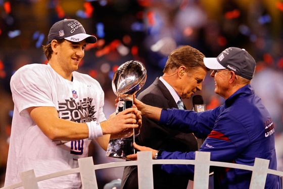 INDIANAPOLIS, IN - FEBRUARY 05:  Eli Manning #10 of the New York Giants poses with the Vince Lombardi Trophy and his head coach Tom Coughlin after the Giants defeated the Patriots by a score of 21-17 in Super Bowl XLVI at Lucas Oil Stadium on February 5, 2012 in Indianapolis, Indiana.  (Photo by Rob Carr/Getty Images)