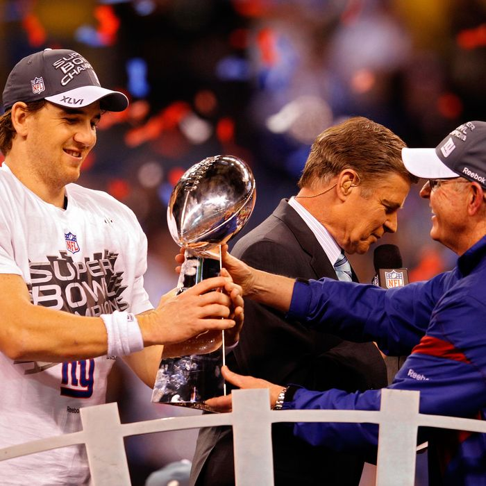 Eli Manning #10 of the New York Giants poses with the Vince Lombardi Trophy and his head coach Tom Coughlin after the Giants defeated the Patriots by a score of 21-17 in Super Bowl XLVI at Lucas Oil Stadium on February 5, 2012 in Indianapolis, Indiana.