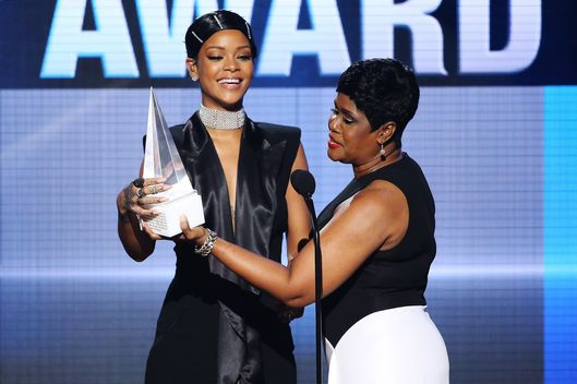Rihanna (L) accepts the AMA Icon Award from her mother, Monica Braithwaite  onstage at the 2013 American Music Awards held at Nokia Theatre L.A. Live on November 24, 2013 in Los Angeles, California.