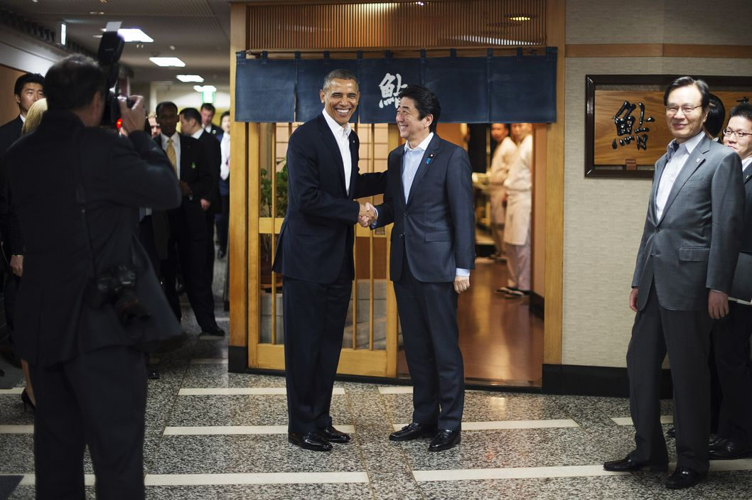 "US President Barack Obama (L) shakes hands with Japanese Prime Minister Shinzo Abe before a private dinner at Sukiyabashi Jiro restaurant in Tokyo on April 23, 2014.   Obama landed in Tokyo on April 23 to launch an Asian tour dedicated to reinvigorating his policy of ""rebalancing"" US foreign policy towards a dynamic Asia.   Sukiyabashi Jiro's less-than-plush surroundings notwithstanding, it is the proud possessor of three Michelin stars, and people flock to pay a minimum $300 for 20 pieces of sushi chosen by the 88-year-old patron, Jiro Ono."