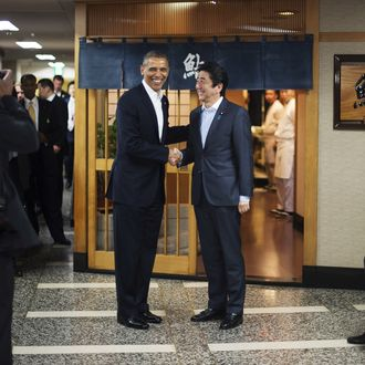 US President Barack Obama (L) shakes hands with Japanese Prime Minister Shinzo Abe before a private dinner at Sukiyabashi Jiro restaurant in Tokyo on April 23, 2014. Obama landed in Tokyo on April 23 to launch an Asian tour dedicated to reinvigorating his policy of