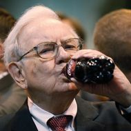 Berkshire Hathaway CEO Warren Buffett drinks a bottle of Coca Cola during at a trade show at the company's annual meeting in Omaha, Nebraska May 3, 2014.