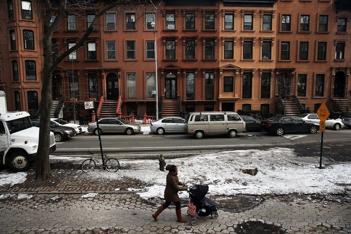 """NEW YORK, NY - FEBRUARY 27: A woman and child walk down a street in the Fort Greene neighborhood where the director and artist Spike Lee once lived on February 27, 2014 in the Brooklyn borough of New York City. During a recent African-American History Month lecture, Lee used strong language to vent his feelings about gentrification in his former neighborhood and other parts of Brooklyn. Numerous Brooklyn neighborhoods, which were once considered dangerous and underdeveloped, have gone through transformations in recent years resulting in more affluent newcomers displacing long time residents. The """"Do The Right Thing"""" director accused many newcomers of not respecting neighborhoods history or character. (Photo by Spencer Platt/Getty Images)"""