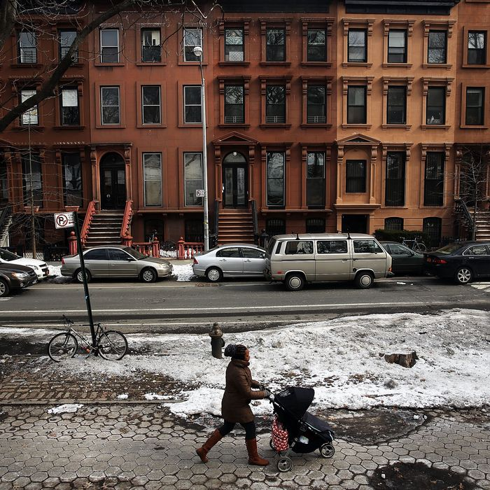 NEW YORK, NY - FEBRUARY 27: A woman and child walk down a street in the Fort Greene neighborhood where the director and artist Spike Lee once lived on February 27, 2014 in the Brooklyn borough of New York City. During a recent African-American History Month lecture, Lee used strong language to vent his feelings about gentrification in his former neighborhood and other parts of Brooklyn. Numerous Brooklyn neighborhoods, which were once considered dangerous and underdeveloped, have gone through transformations in recent years resulting in more affluent newcomers displacing long time residents. The