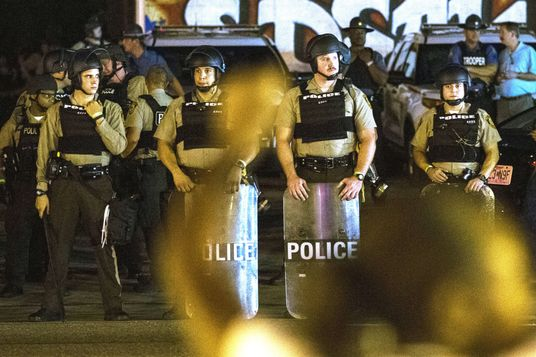 St Louis County police officers watch as anti-police demonstrators march in protest in Ferguson, Missouri