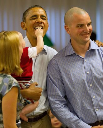 KANEOHE, HI - DECEMBER 25: Eight-month-old Cooper Wall Wagner sticks his fingers in U.S. President Barack Obama's mouth as the President poses for a picture with Cooper's parents, Greg and Meredith Wagner, on December 25, 2011 in Kaneohe, Hawaii. The President and Mrs. Obama make their annual trip to greet current and retired members of the U.S. military and their families as they eat a Christmas Day meal in the Anderson Hall mess hall at Marine Corps Base Hawaii. (Photo by Kent Nishimura-Pool/Getty Images)