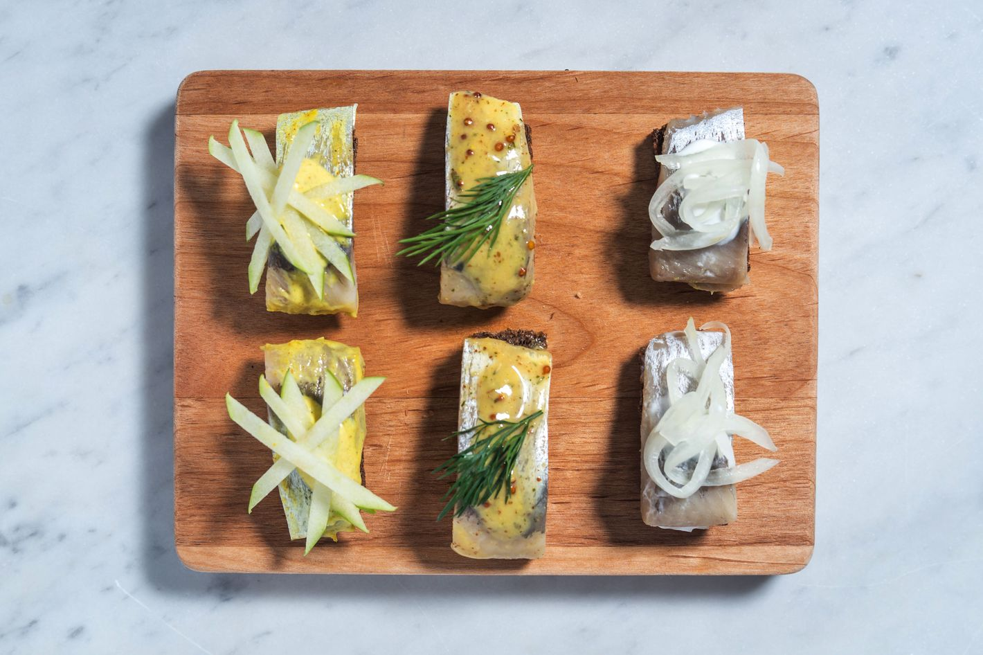 Canapés of pickled herring on pumpernickel bread: mustard and dill herring; curry herring with green apple; and pickled herring with cream sauce and pickled onions.
