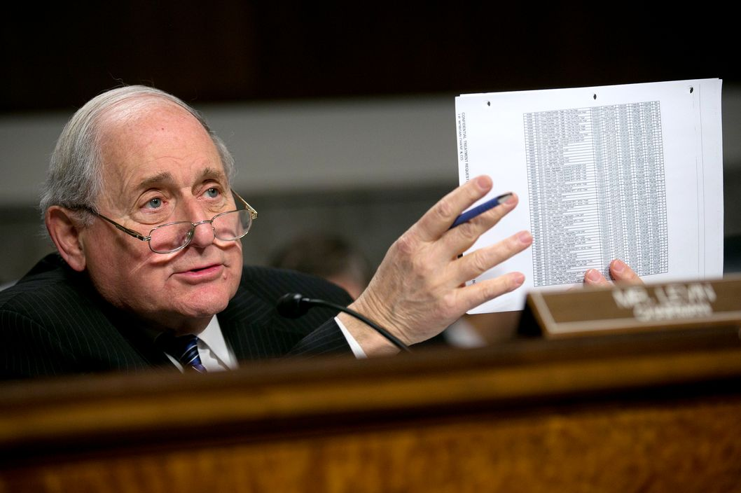 Senator Carl Levin, a Democrat from Michigan, holds up documents while questioning witnesses during a Senate Permanent Subcommittee on Investigations hearing in Washington, D.C., U.S., on Friday, March 15, 2013. JPMorgan Chase & Co.'??s, the biggest U.S. bank by assets, compensated chief investment office traders in a way that encouraged risk-taking before the unit amassed losses exceeding $6.2 billion, a Senate committee said.