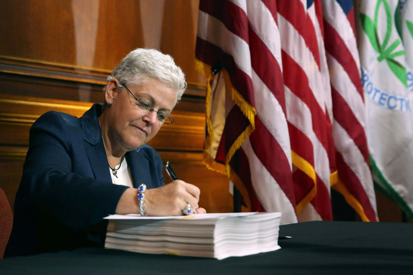 U.S. Environmental Protection Agency Administrator Gina McCarthy signs new regulations for power plants June 2, 2014 in Washington, DC. Bypassing Congress and using President Barack Obama's 'Climate Action Plan,' the new regulations will force more than 600 existing coal-fired power plants, the single largest source of greenhouse gas emission in the country, to reduce their carbon pollution 30 percent from 2005 levels by 2030.