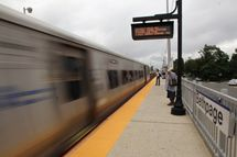 BETHPAGE, NY - AUGUST 27: Riders get ready to board a Long Island Rail Road train prior to the planned noon shutdown on August 27, 2011 in Bethpage, New York. Irene, now a Category 1 hurricane, has made landfall in North Carolina on its way up the eastern seaboard.  (Photo by Bruce Bennett/Getty Images)