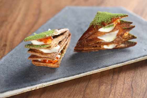 The millefeuille layers bechamel sauce, trout roe, and yuzukosho between rye-flour puff pastry. That's matcha tea dusted on top.
