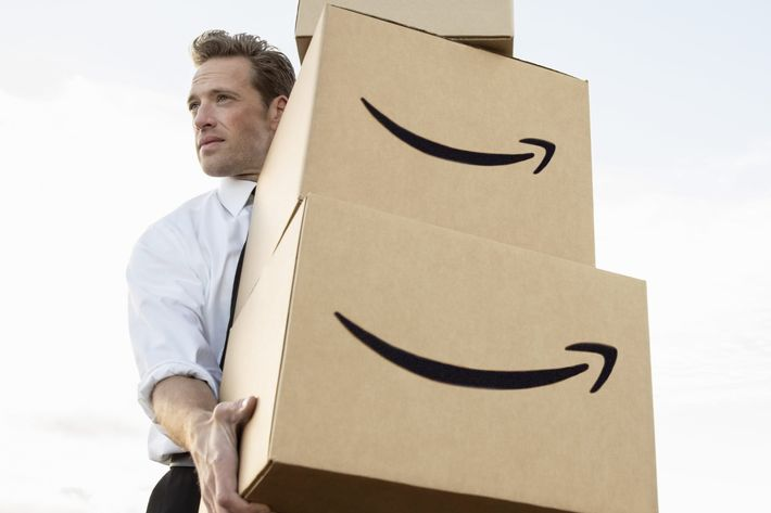Businessman carrying stacked boxes on field