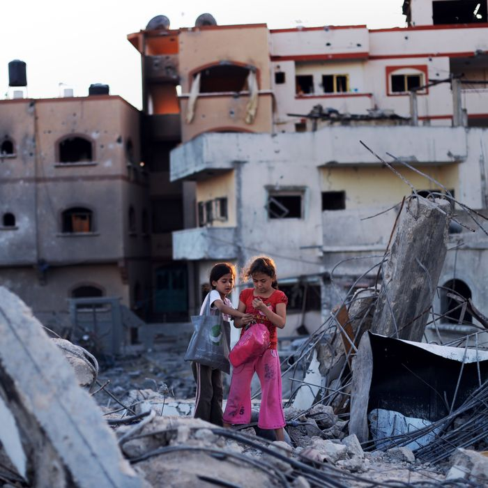 Shahed Abood (R), 7, and her cousin Ali (L), 9, look at some of the belonging they salvaged from their destroyed homes on August 11, 2014 in Jabalia, northern Gaza Strip. The girls and their families sought refuge in a UN school fled their neighborhood when fighting broke out between Israel military and Hamas a little over 4 weeks ago. A fresh 72-hour ceasefire between Israel and Hamas came into effect in Gaza today, paving the way for talks in Egypt aimed at a durable end to a month-long conflict that has wreaked devastating bloodshed. AFP PHOTO/ROBERTO SCHMIDT (Photo credit should read ROBERTO SCHMIDT/AFP/Getty Images)