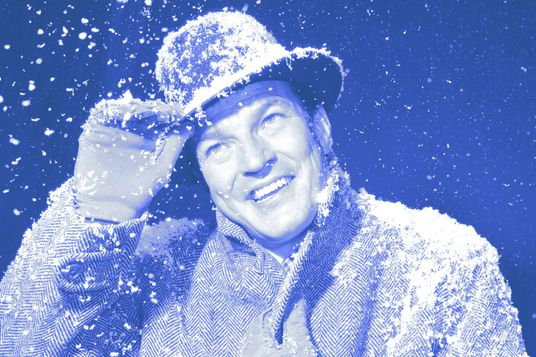 1950s 1960s smiling man outside in hat overcoat and gloves while snowing