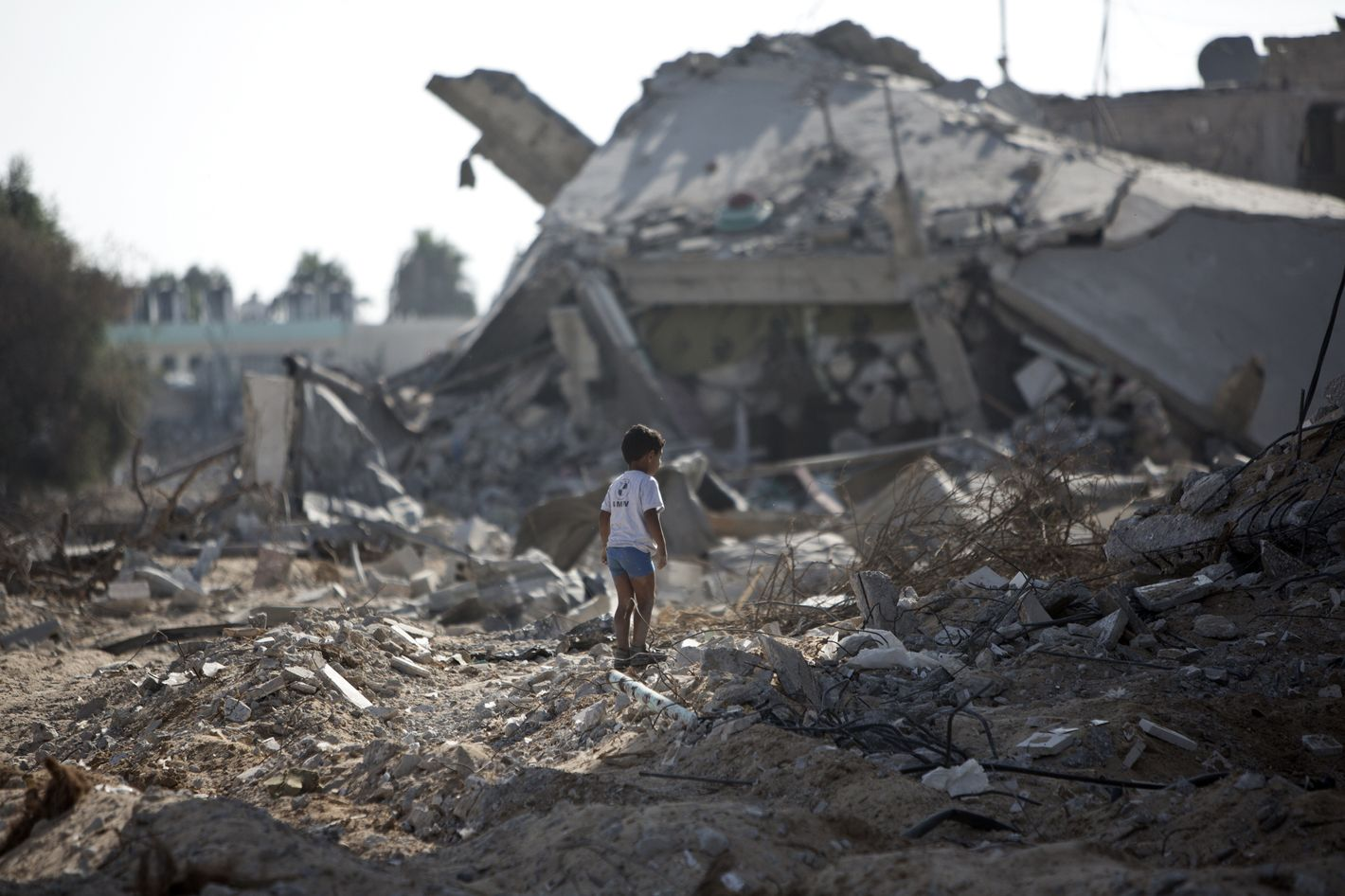 A Palestinian boy walks over debris as civilians who were displaced from their houses due to fighting between Israel's army and Hamas fighters return to check their homes in Gaza City's Shejaiya neighbourhood, on August 1, 2014. Israeli shelling killed eight people in Gaza today just hours into a three-day truce, medics said, as a diplomatic push for a more durable end to the bloodshed gained pace.  It gave a brief respite to residents of the battered strip, after 25 days of violence that killed 1,459 on the Palestinian side, mostly civilians, and 61 soldiers and three civilians on the Israeli side. AFP PHOTO / MAHMUD HAMS        (Photo credit should read MAHMUD HAMS/AFP/Getty Images)