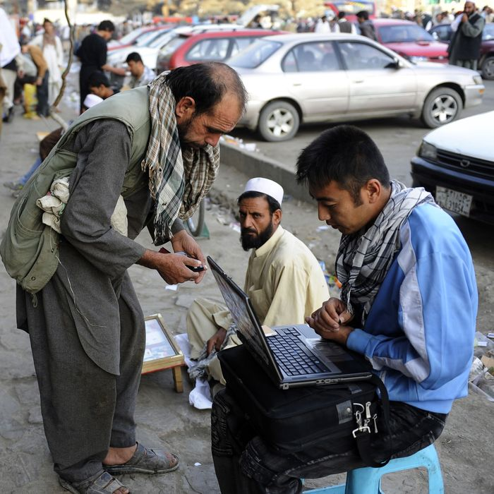 An Afghan street vendor sells music he uploads to customers' mobile phones in downtown Kabul.