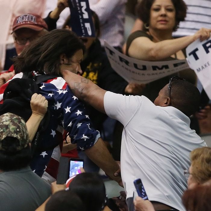 Trump protester Bryan Sanders, center left, is punched by a Trump supporter as he is escorted out of Republican presidential candidate Donald Trump's rally at the Tucson Arena in downtown Tucson, Ariz., Saturday, March 19, 2016. (Mike Christy/Arizona Daily Star via AP) MANDATORY CREDIT
