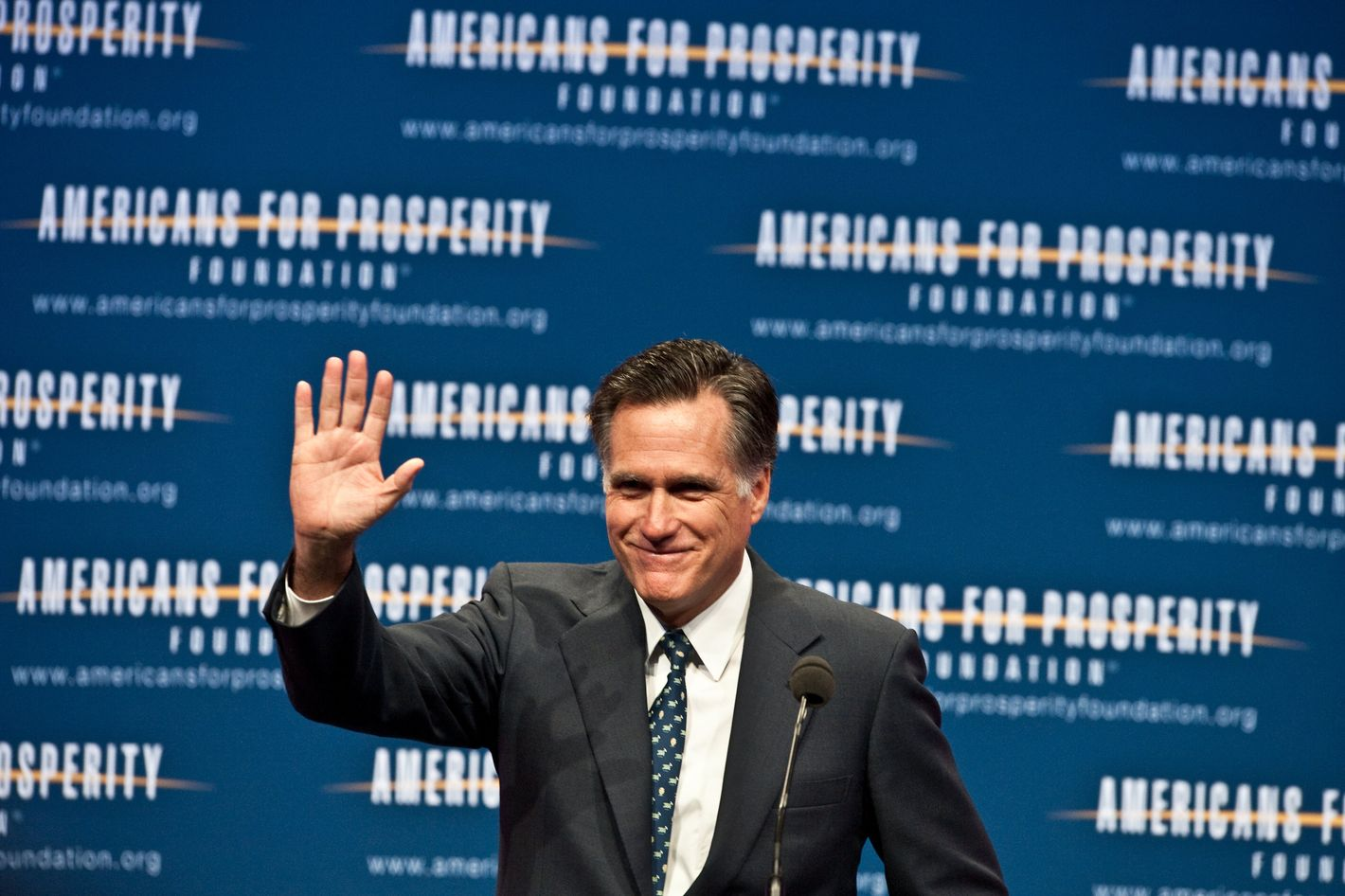 "US Republican presidential hopeful Mitt Romney acknowledges the crowd after addressing the ""Defending The American Dream Summit"" organized by the conservative Americans For Prosperity (AFP) foundation in Washington,DC on November 4, 2011. Romney on Friday laid out his vision for ""simpler, smaller and smarter"" government, vowing to raise the retirement age and eliminate federal agencies. Unveiling his plan to trim the US deficit by $500 billion by 2016, Romney said he would raise the retirement age for the next generation, cut bureaucracy and change the constitution to make balanced budgets compulsory. AFP PHOTO/Nicholas KAMM (Photo credit should read NICHOLAS KAMM/AFP/Getty Images)"