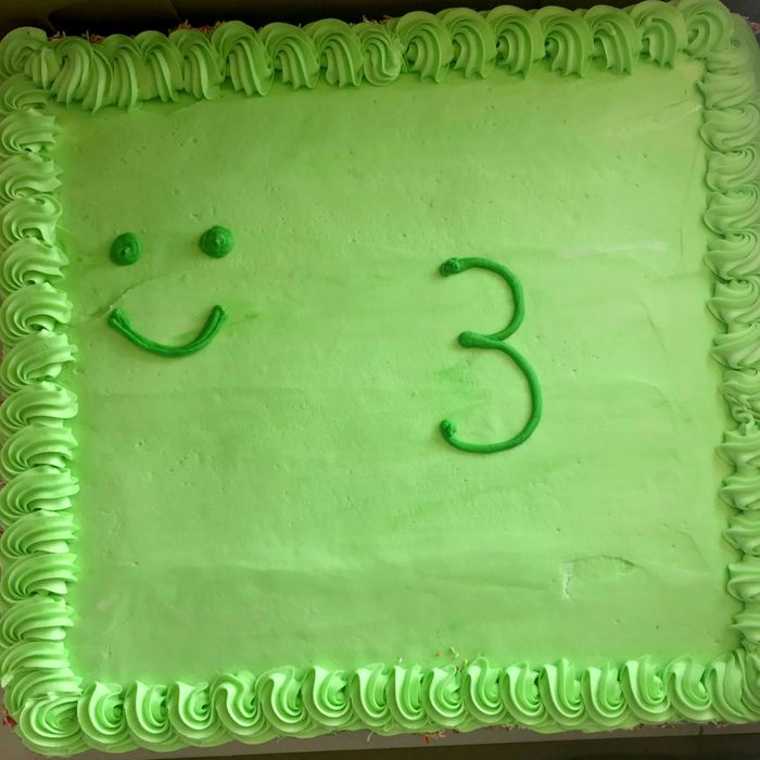 A cake with a smiley face and a number 3.