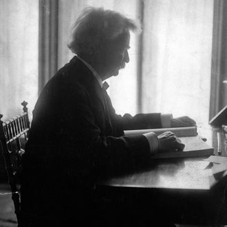 Profile of Mark Twain seated at a desk, reading a large book, 1906.