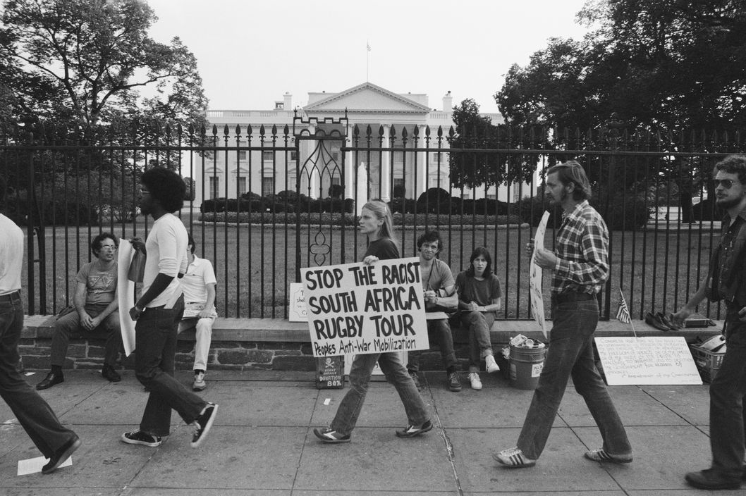 Outside the White House, an anti-apartheid demonstrator carries a placard protesting against the US tour by South African rugby team, the Springboks, Washington DC, 1st September 1981. (Photo by Jonathan C. Katzenellenbogen/Getty Images)