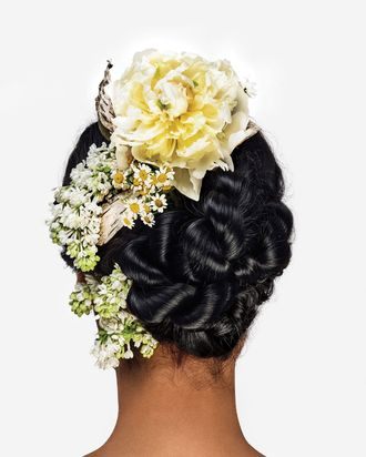 A knotted updo with lilacs and peonies.