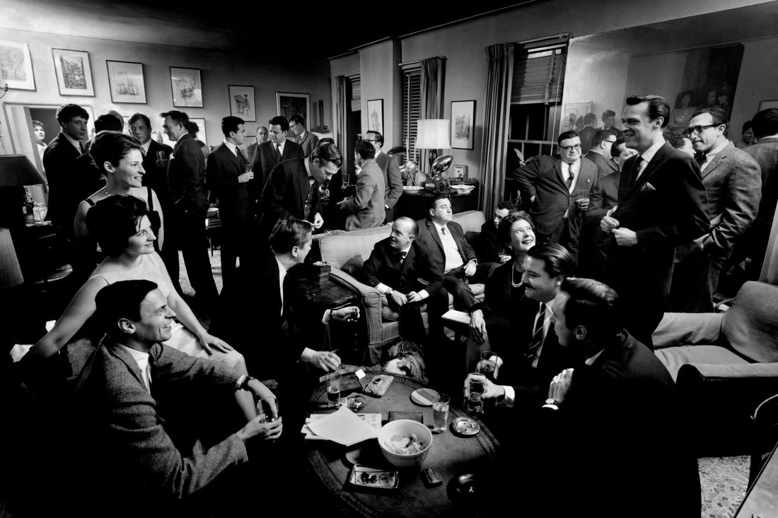 USA. New York City. 1963. Literary cocktail party at George PLIMPTON's Upper East Side apartment. Plimpton is seated at left with literary agent Maggie ABBOTT next to him. At top, left to right: Jonathan MILLER, Gore VIDAL, Ricky LEACOCK, Robert LASKEY, and Paul HELLER. In background, left to right: Ralph ELLISON and Peter MATTHIESEN. Center: Walter BERNSTEIN (seated on couch with back to camera); Sydney LUMET (behind Bernstein to right); Mario PUZO (leaning against mirror); Jack RICHARDSON (tall man, front, right foreground); Arthur KOPITT (foreground, right); Frank PERRY (left of Kopitt); Eleanor PERRY (left of Frank); Arthur PENN (obscured behind Eleanor) and Truman CAPOTE (center on couch).