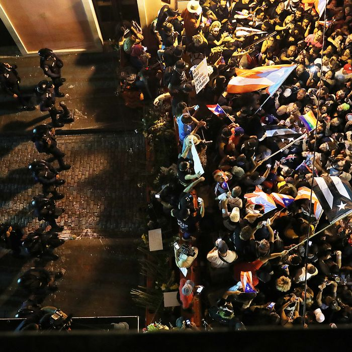 Protesters demonstrate near a police barricade on a street leading to the governor's mansion.