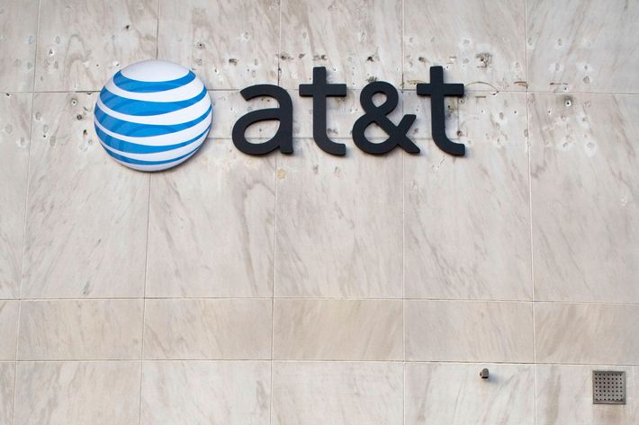 A pedestrian walks by an AT&T store in Downtown Brooklyn section of New York, U.S. on Tuesday, Dec. 11, 2007. Photographer: Ramin Talaie