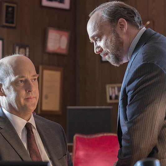 Paul Giamatti as Chuck Rhoades and Anthony Edwards as Judge Wilcox.